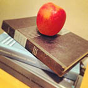 Pile of books with an apple on top.